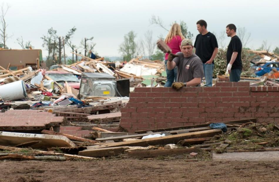 A man casts aside bricks while searching in the rubble of a house destroyed by a tornado in the...