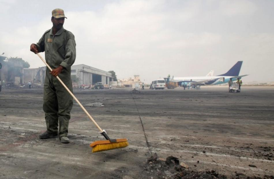 A man clears debris from the tarmac of Jinnah International Airport, after the attack by Taliban...