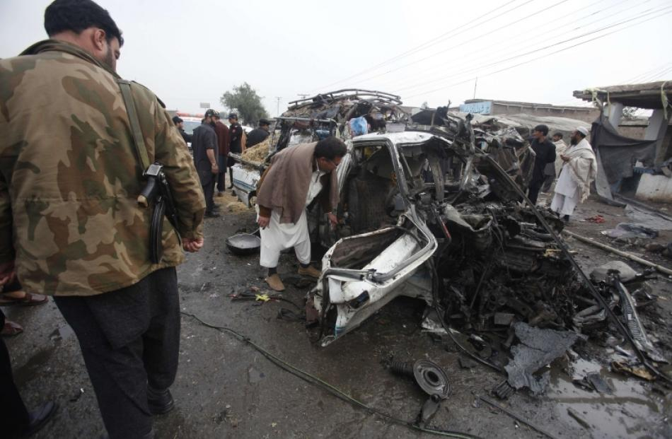 A man looks into a car, which was damaged during a bomb attack at Fauji Market in Peshawar. Photo...
