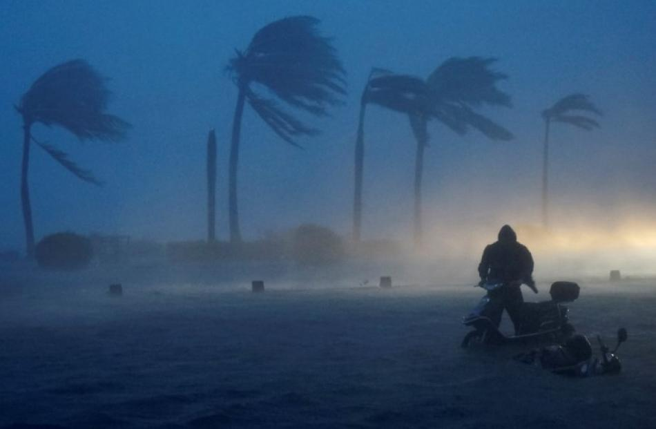A man pushes his electric bicycle along a flooded seaside street as Typhoon Rammasun hits in...
