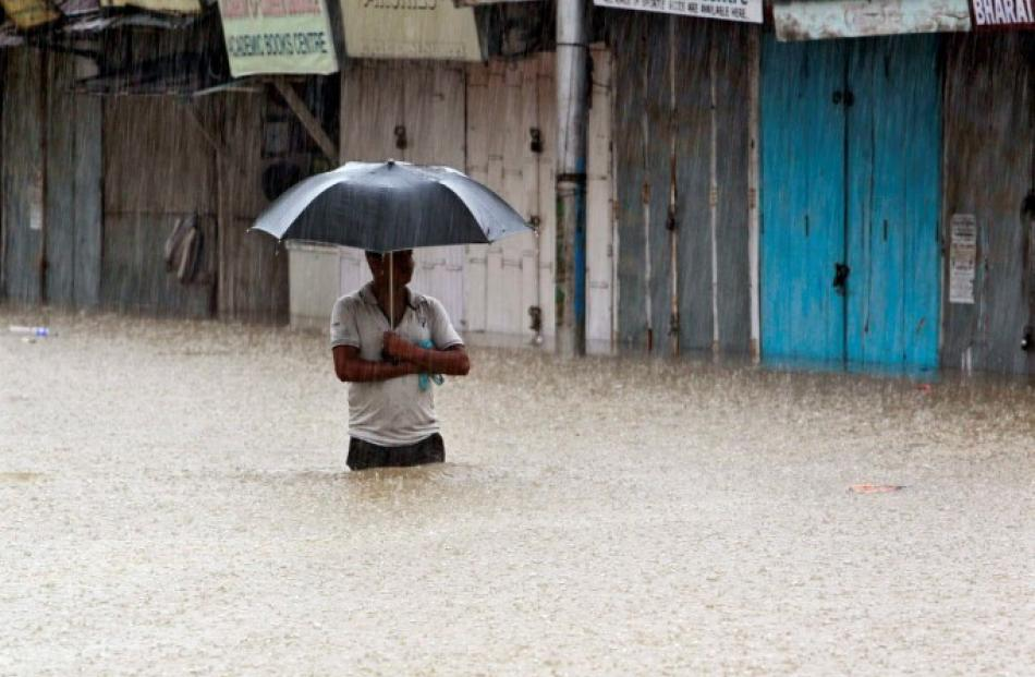 A man wades through a flooded street during a heavy monsoon rain shower in Agartala, capital of...