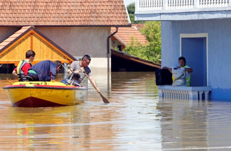 A man waits to be rescued from his house during heavy floods in Vojskova, Bosnia. REUTERS/Srdjan...