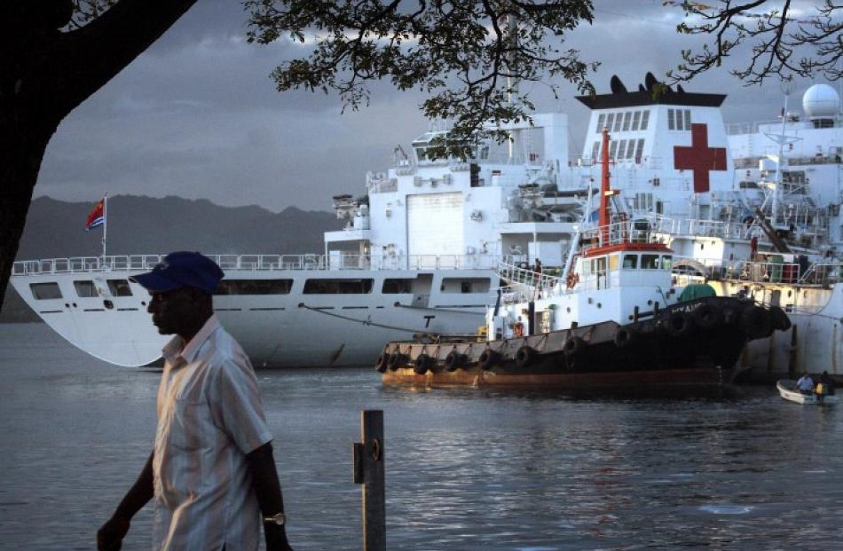 A man walks past The Peace Ark, a Chinese hospital ship which offers free health care as it sails...
