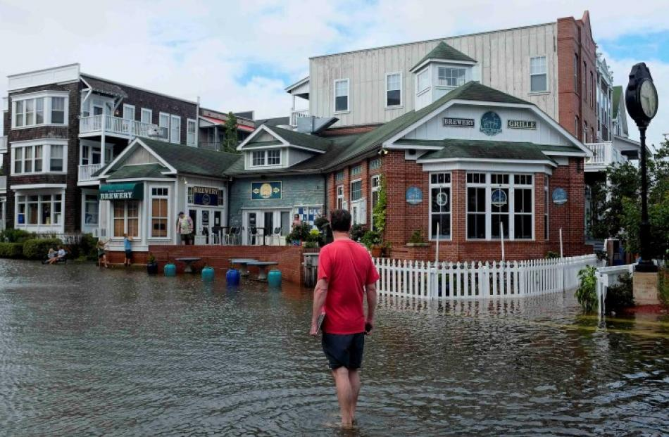 A man walks through a flooded street after Hurricane Arthur passed through in Manteo, North...