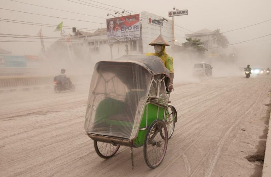 A man wears a mask as he rides a becak, a kind of rickshaw, on a road covered with ash from Mount...