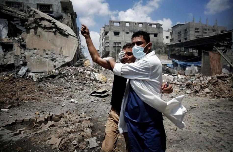 A medic helps a Palestinian in the Shejaia neighbourhood, which was heavily shelled by Israel...