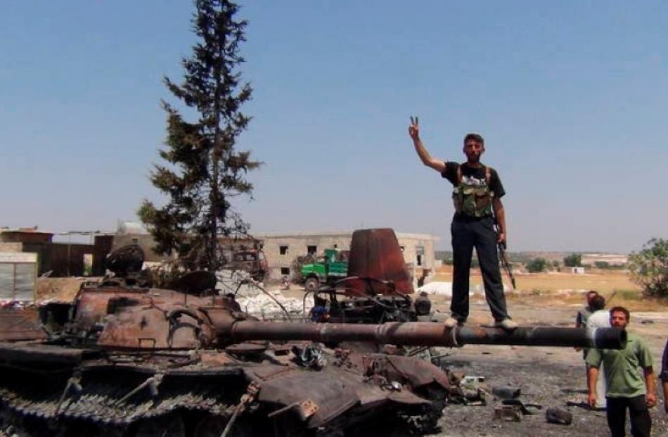 A member of the Free Syrian Army stands on a damaged tank in Jerjenaz, near Idlib. REUTERS/Shaam...