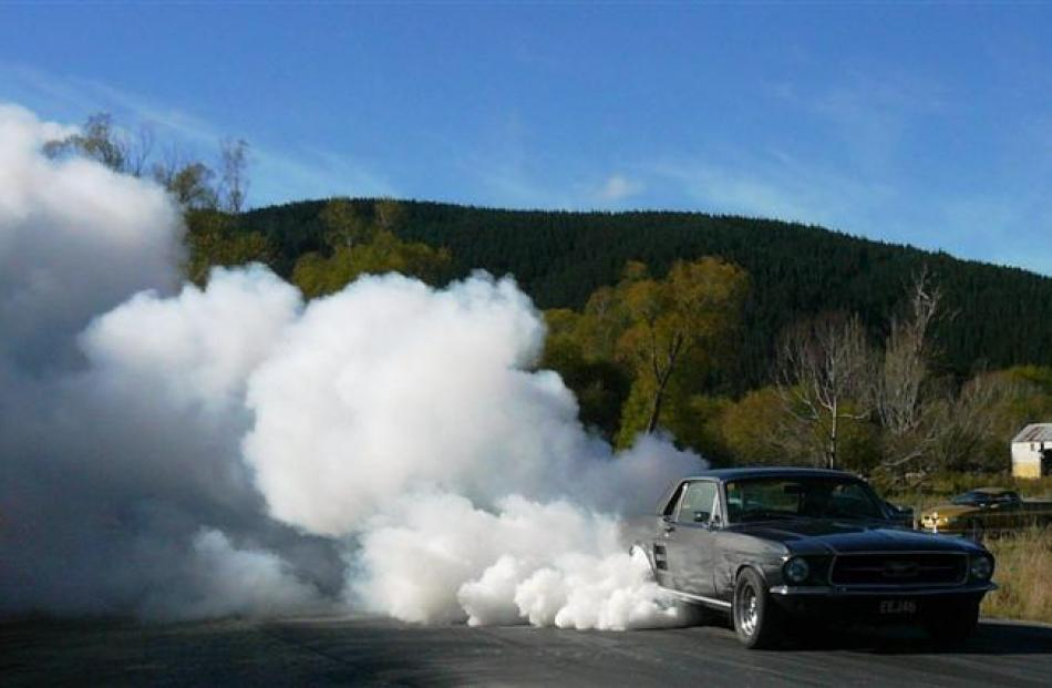 A Mustang creates a plume of smoke at the Lawrence quarter-mile sprints last year. Photo by Kim...