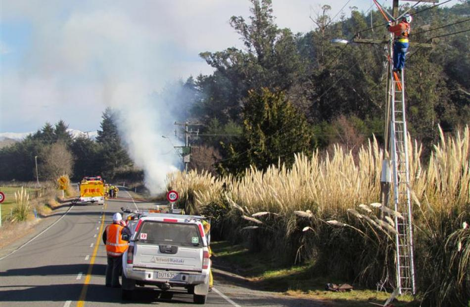 A Network Waitaki linesman (right)  disconnects electricity from a power line on the Weston...