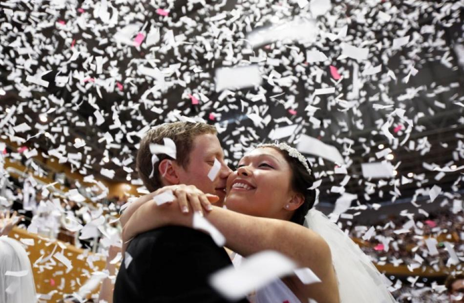 A newlywed couple celebrates during a mass wedding ceremony of the Unification Church at...