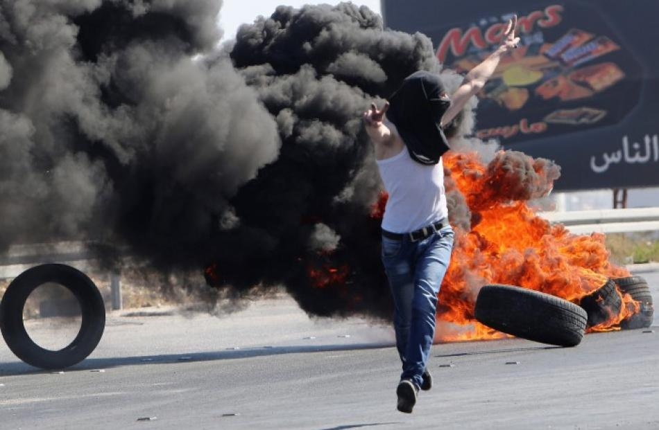 A Palestinian protester gestures to Israeli soldiers during a protest against the Israeli...