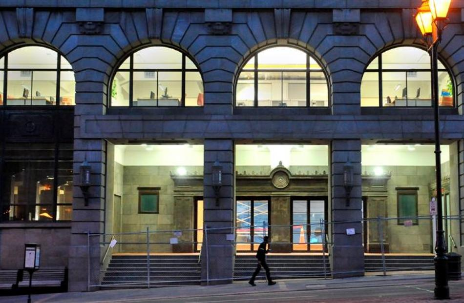 A pedestrian walks past Dunedin's former chief post office building last night. About 145 staff...