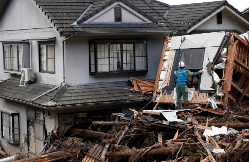 A police officer searches for survivors at a site where a landslide swept through a residential...