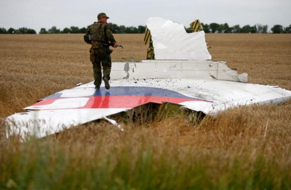 A pro-Russian separatist stands on part of the wreckage of the Malaysia Airlines Boeing 777 near...
