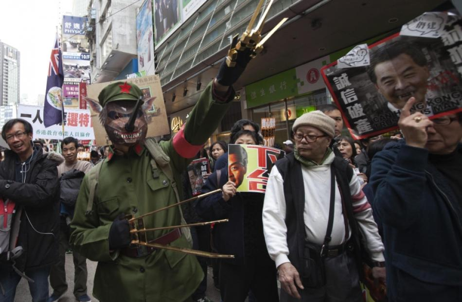 A protester dressed as a cultural revolution red guard wearing a wolf mask gestures during a...