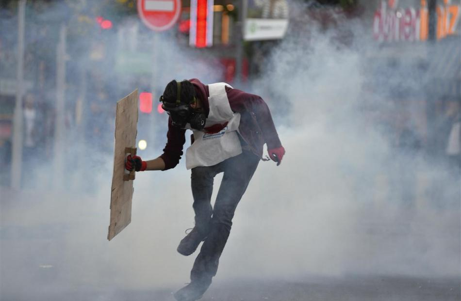 A protester runs away from tear gas fired by riot police during a demonstration blaming the...
