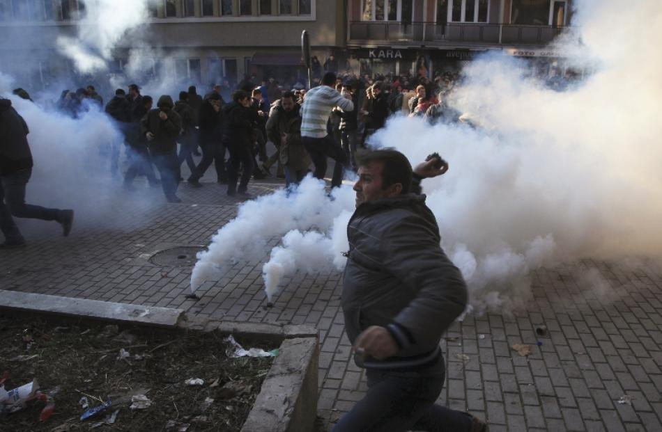 A protester throws rocks at police officers during clashes in the rectorate's courtyard at the...
