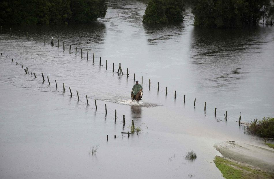 A resident rides his horse along a flooded road near Puerto Varas city, south of Santiago....