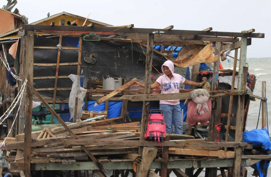 A resident salvages her belongings inside a damaged house after strong winds brought by Typhoon...
