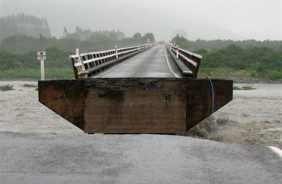 A section of the Wanganui River bridge, near Harihari, on the West Coast, was swept away by...