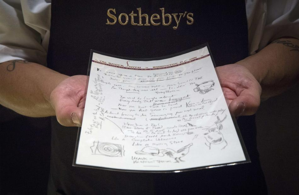 A Sotheby's employee shows the handwritten lyrics for Bob Dylan's 'Like a Rolling Stone' song...