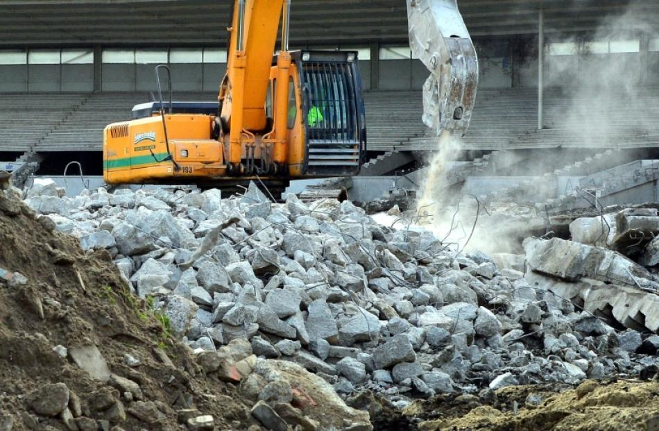 A Southern Demolition excavator turns the Carisbrook terrace to rubble yesterday. Photo by...