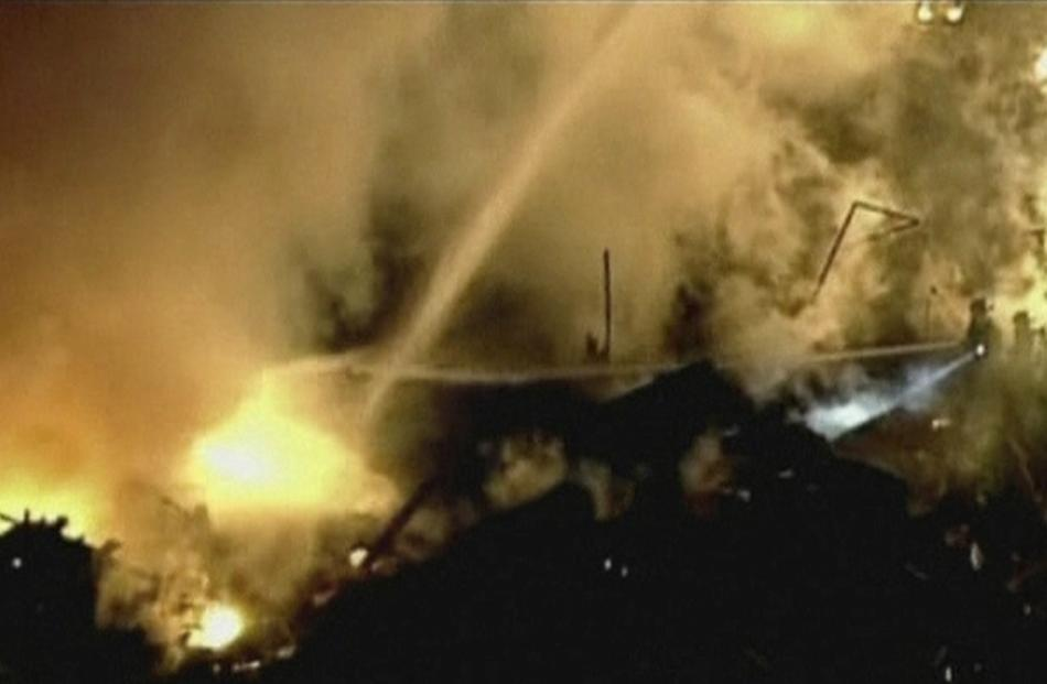 A still image taken from a KHSB-TV video footage shows aerial of the flames and firefighters...