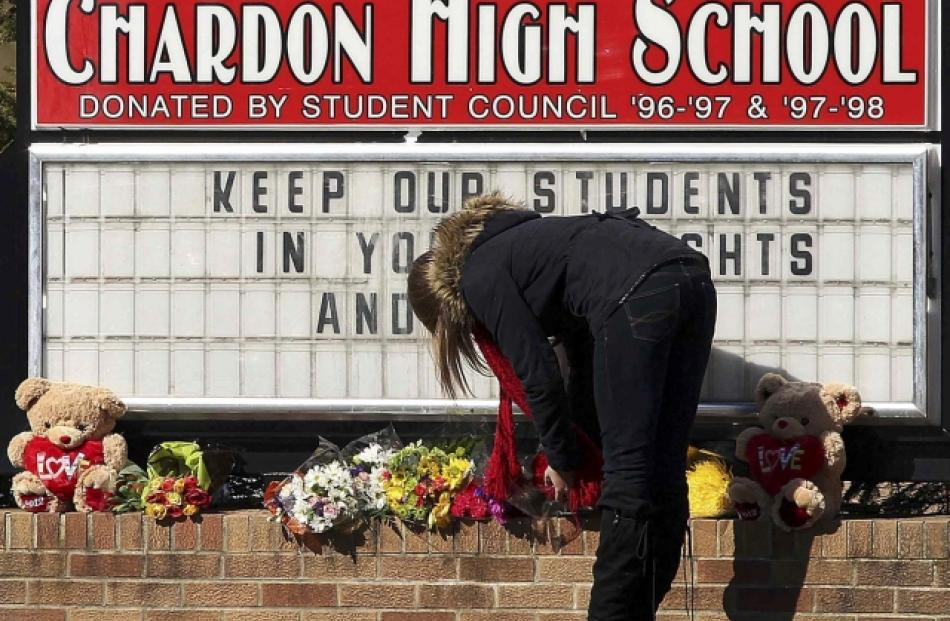 A student places a bouquet of roses at the base of the Chardon High School sign in Chardon, Ohio...