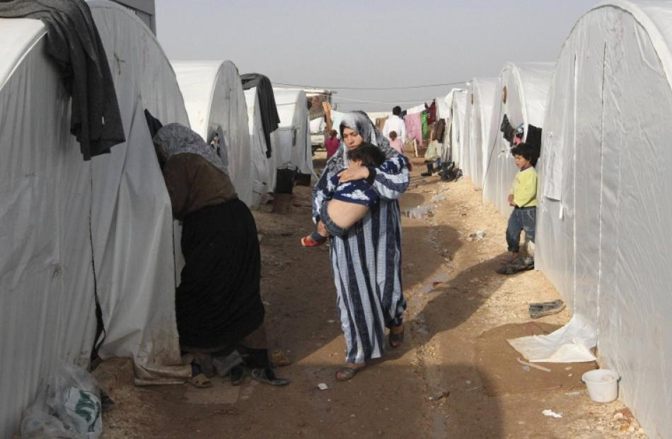 A Syrian refugee woman holds her child in the refugee camp of Bab El Salama, between the Syrian...