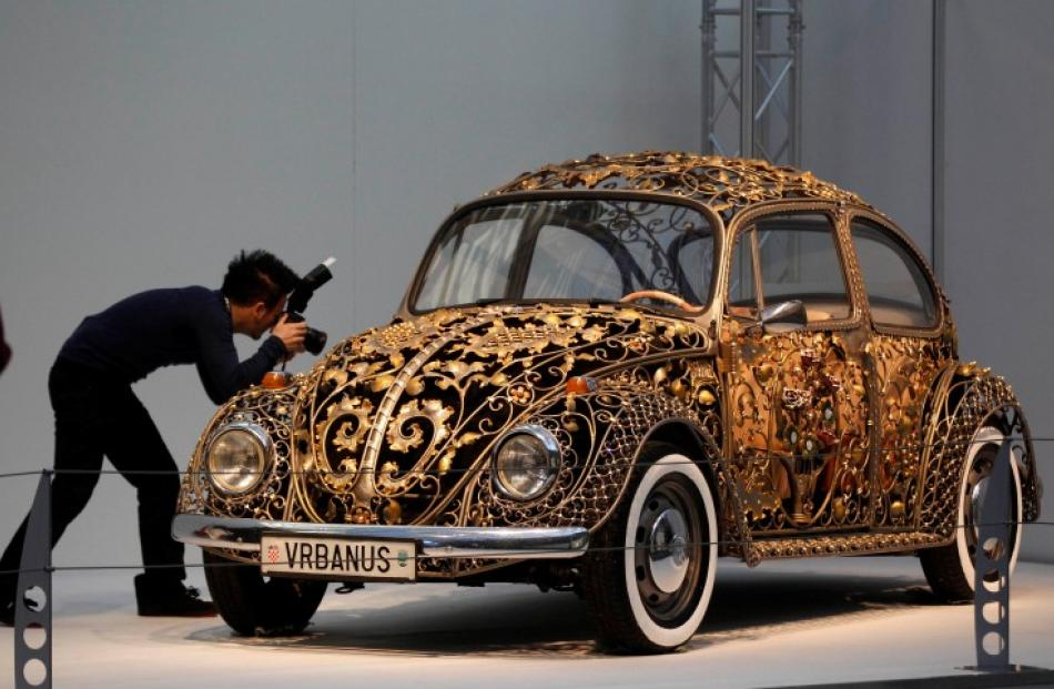 A visitor takes a picture at a modified Volkswagen VW Beetle before the show. REUTERS/Ina Fassbender
