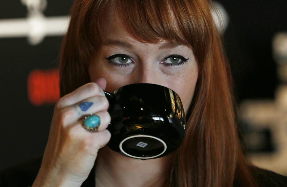 A woman drinks tea in a T2 shop in London. REUTERS/Stefan Wermuth
