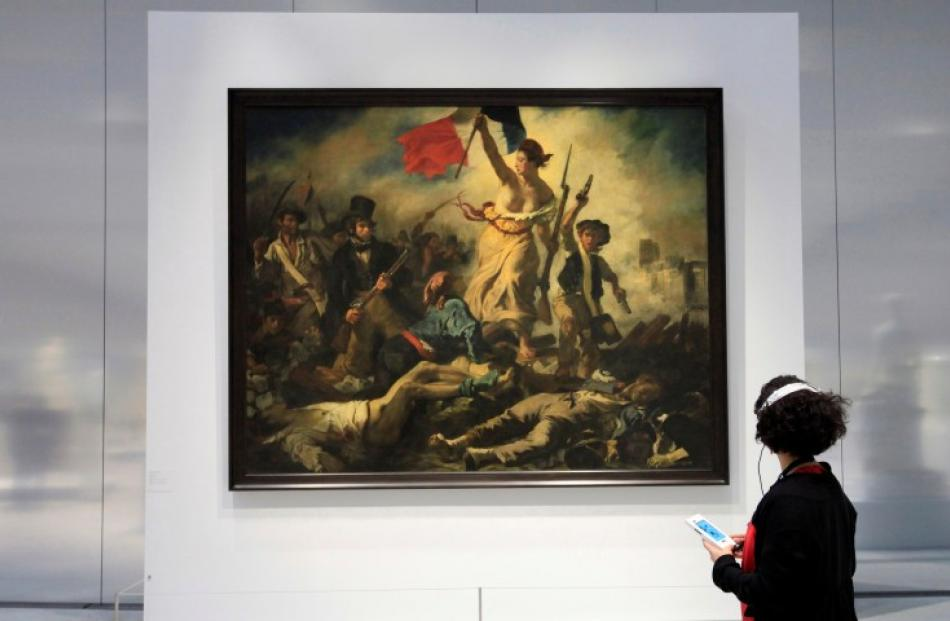 A woman looks at Eugene Delacroix's 'Liberty Leading the People' in the Le Louvre Lens Museum, in...