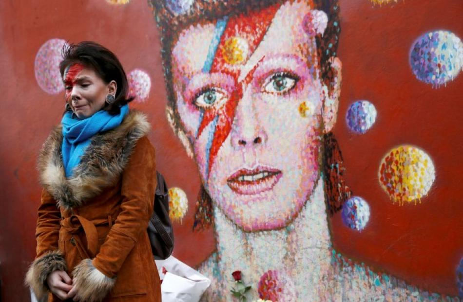 A woman wearing Ziggy Stardust-style make-up mourns by a mural of David Bowie in Brixton, south...
