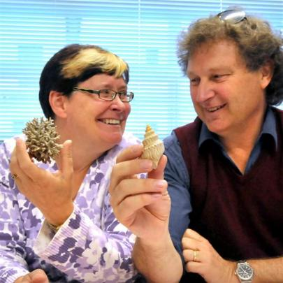 Abby Smith and Hamish Spencer hold examples of bryozoa and marine snails similar to those named...