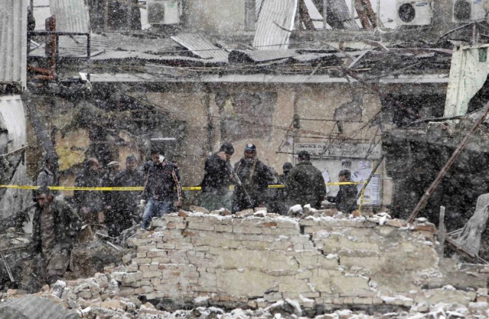 Afghan policemen investigate the site of an explosion in Kabul. Photo by Reuters