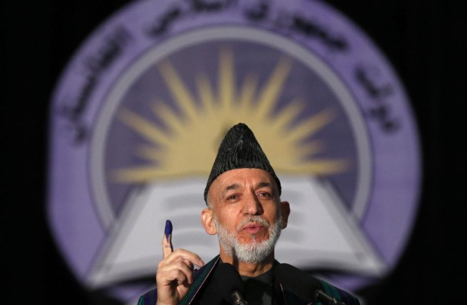 Afghan President Hamid Karzai holds up his inked stained finger after voting in the presidential...