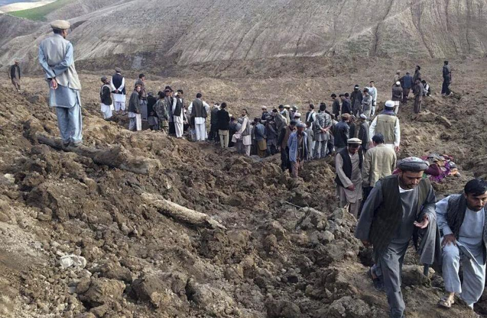Afghan villagers gather at the site of a landslide at the Argo district in Badakhshan province....
