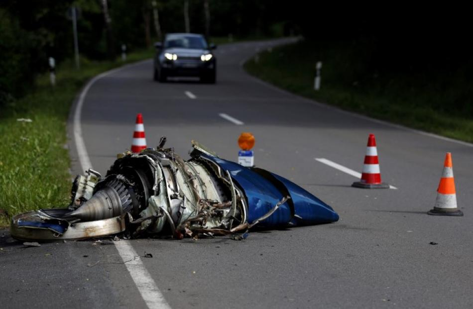 Aircraft parts lie on a road in Elpe, near the western city of Olsberg, after the mid-air...