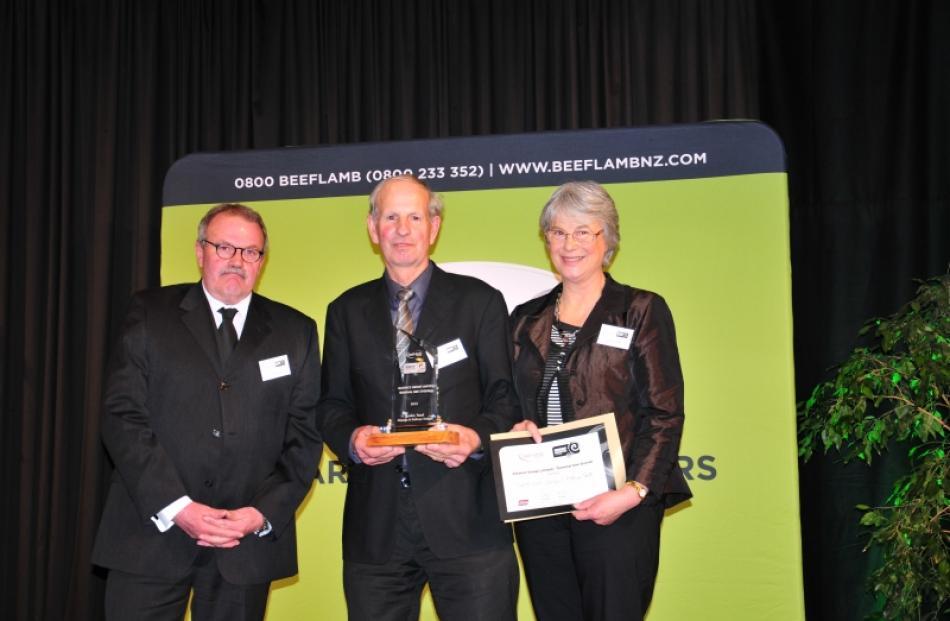 Alliance Group chairman Owen Poole presents Mimihau farmers George and Kathryn Smith  with three...