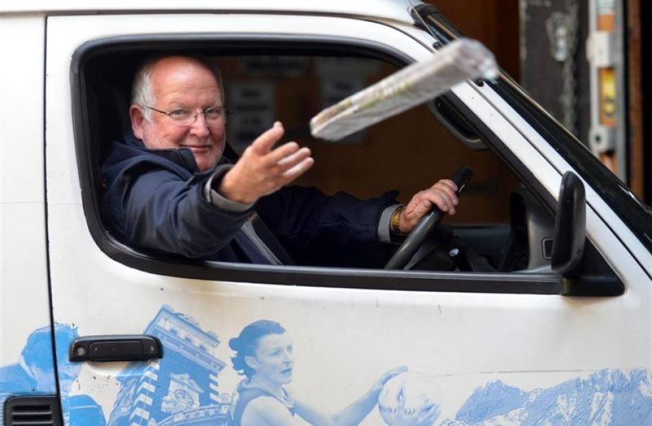 Allied Press distribution manager Warren Godfrey tosses a newspaper from a delivery van for the...