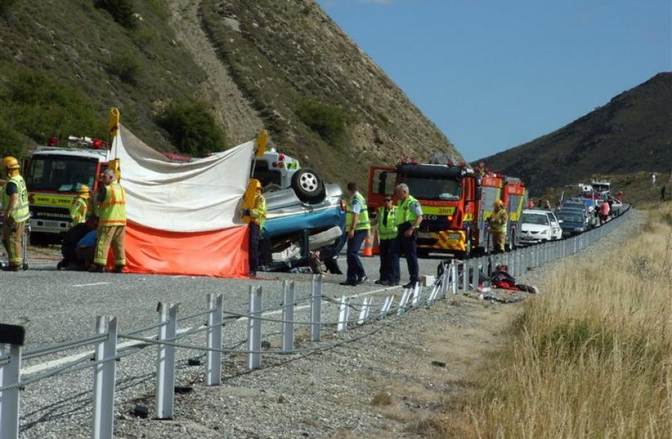 Ambulance staff treat two injured German tourists beside their overturned vehicle. Several metres...