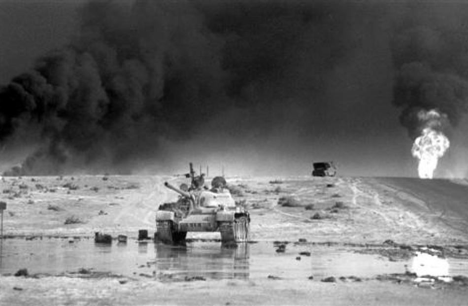 An abandoned Iraqi tank in front of burning oil wells south of Kuwait City, Iraq, in 1991. Photo...