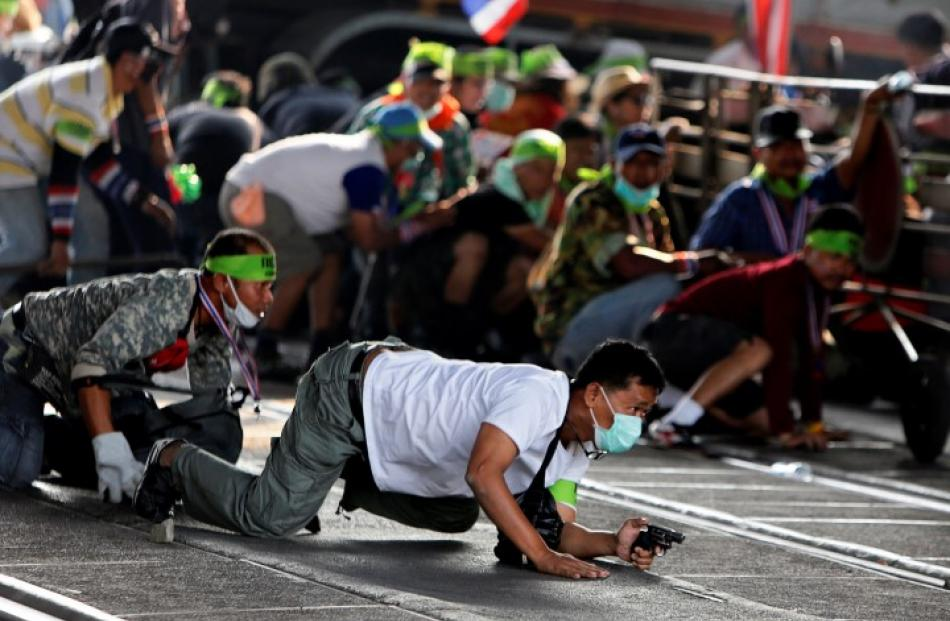 An anti-government protester crawls with his pistol during a gunfight between supporters and...