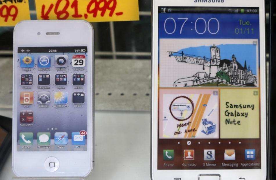 An Apple iPhone (left) and a Samsung Galaxy Note are displayed at a shop in Tokyo. File photo by...
