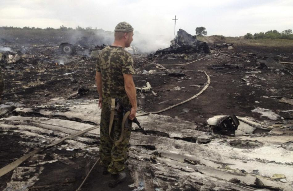 An armed pro-Russian separatist stands at a site of a Malaysia Airlines Boeing 777 plane crash in...
