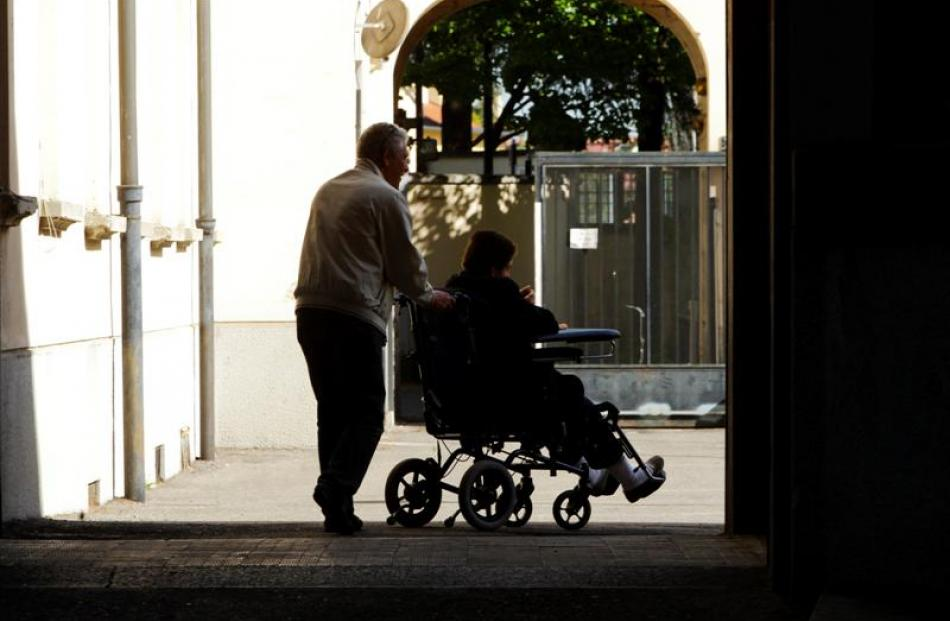 An assistant pushes a woman in her wheelchair at the Sacred Family Foundation, where former Prime...