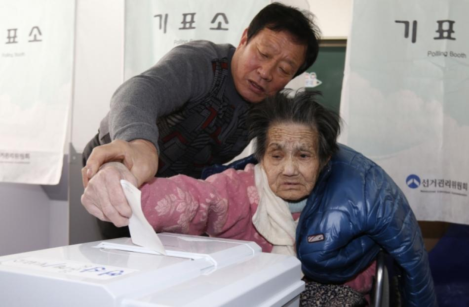 An elderly woman is assisted in casting her ballot in the presidential election at a polling...
