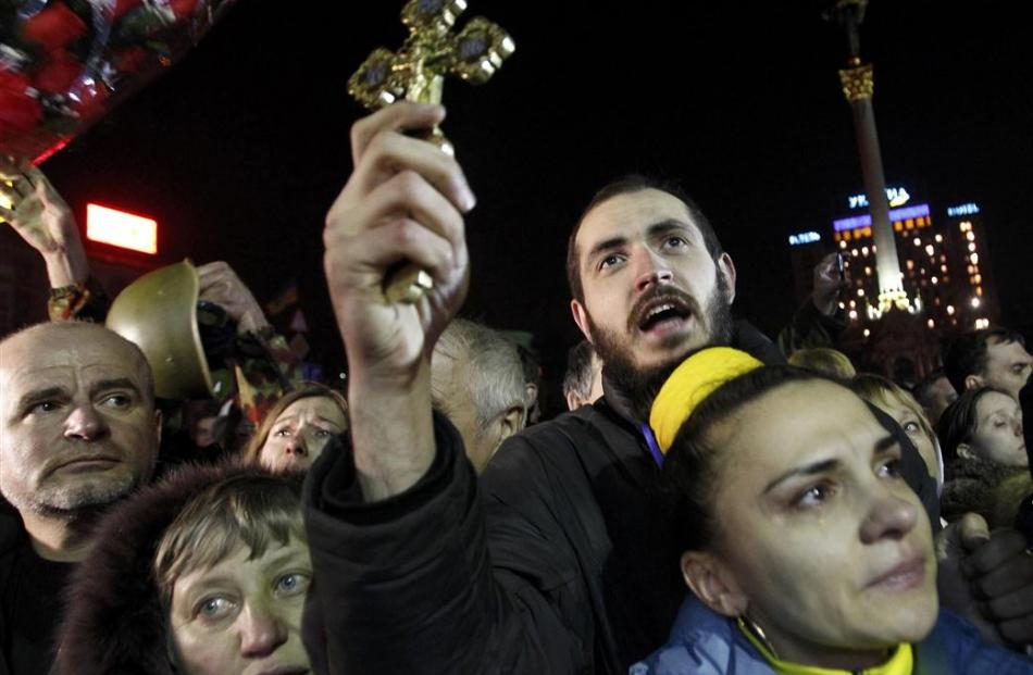 Anti-government protesters sing during a rally in central Independence Square in Kiev .   ...