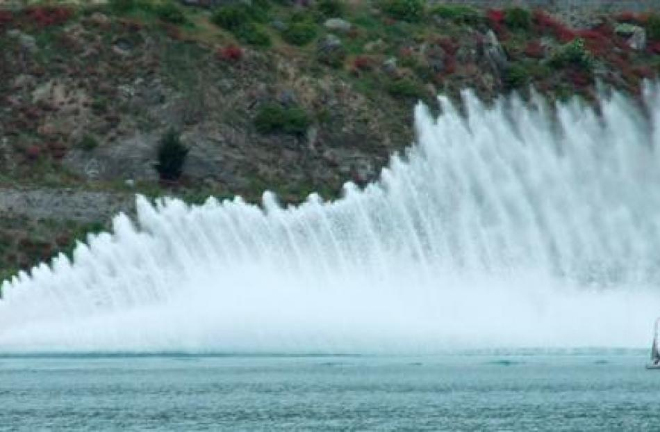 An official's boat on Lake Dunstan is dwarfed by the shower of spray from hydroplane The Boss,...