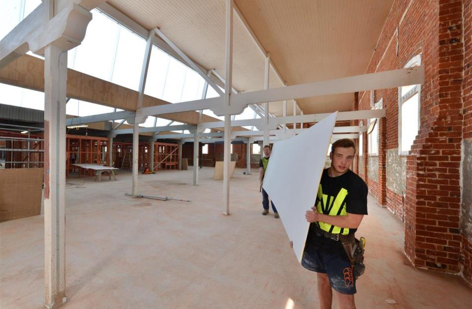 Apprentice carpenters Jared Fahey (foreground) and Jack Pollock carry plasterboard across the ...